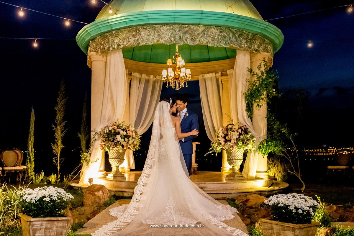 Fotos realizadas apos a cerimonia o casal faz poses para as lentes do magnifico fotografo de casamento Sandro Andrade, fotografo em Bsb no Df. Linda fotografia no gazebo com a noiva de costas mostrando todos os detalhes do vestido e da mantilha.