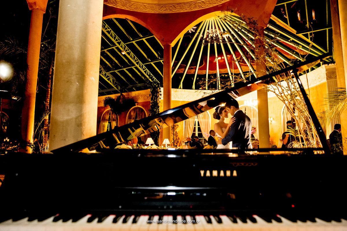 Eles dançam, cheios de amor! Fotografia de Sandro Andrade, fotografia criativa e artistica colocando os noivos ao fundo do piano, simplesmente linda!