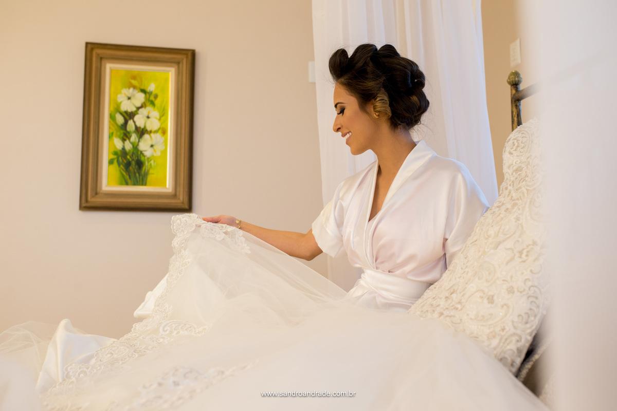 Ansiosa ela admira seu lindo vestido de noiva, na suite da noiva do Le Blanc Cabelo e Maquiagem no Gama.