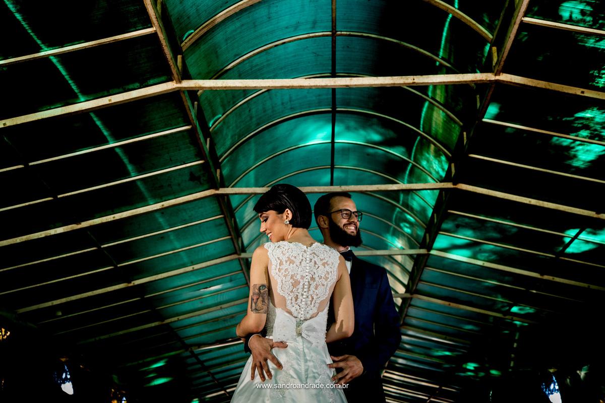 Casal lindo, detalhe do vestido da noiva nas costas, beleza exótica.