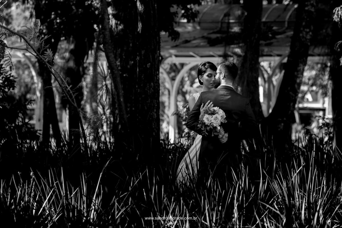 Uma linda fotografia dos noivos em meio as arvores em uma linda imagem preto e branca, muito amor demonstrado nessa foto.