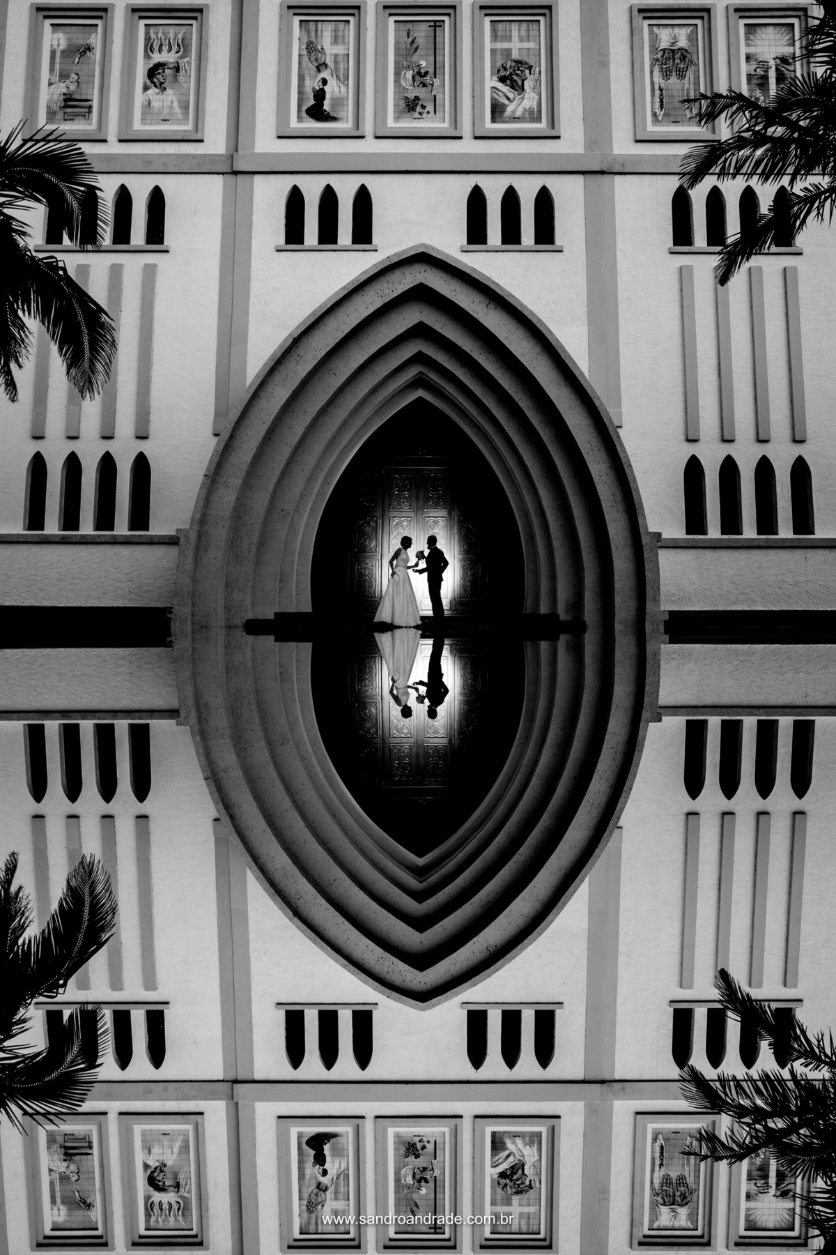 Ainda a porta da igreja, uma belissima fotografia de reflexo com os noivos a porta em preto e branco.