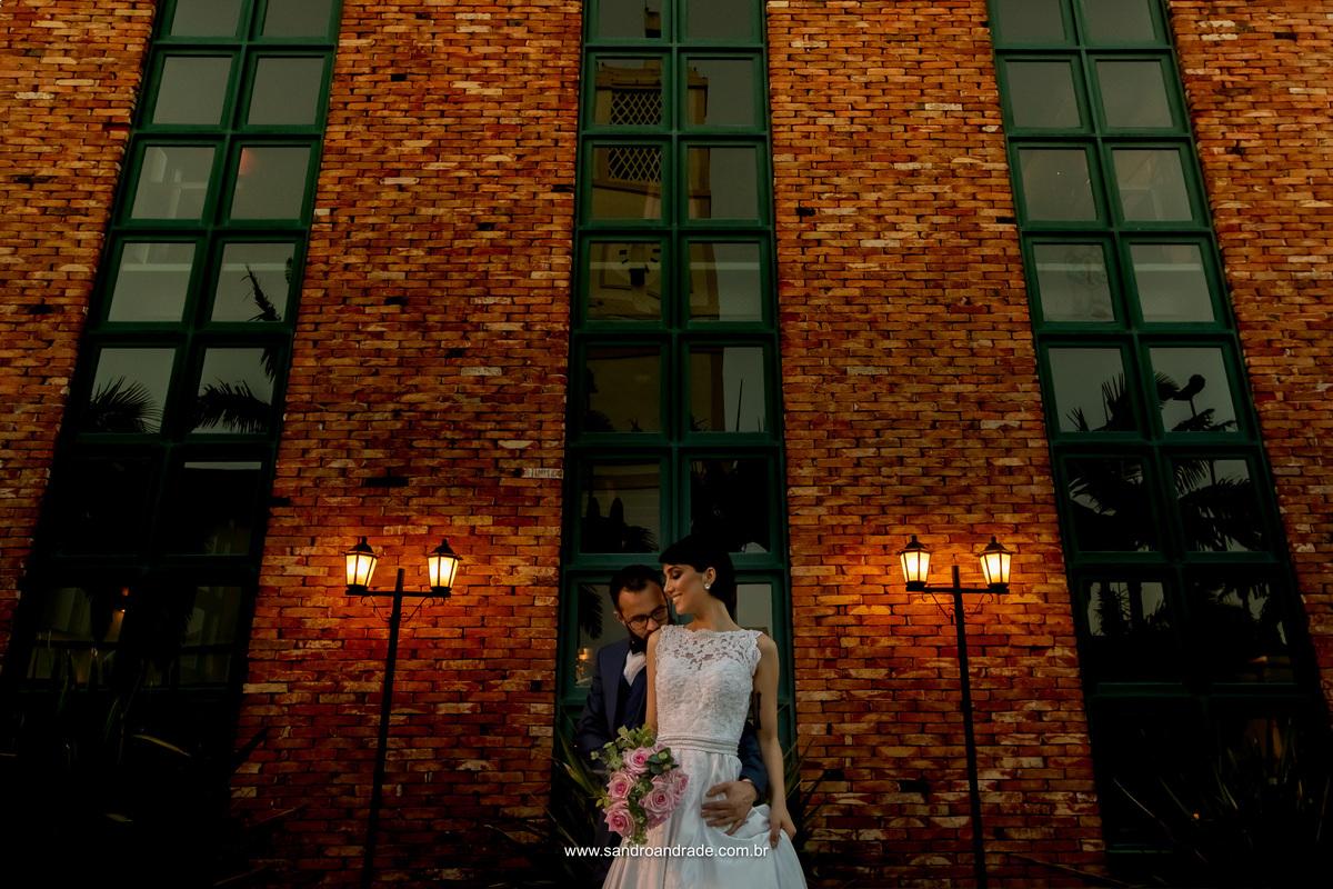 Os noivos em contraste com os tijolinhos vermelhos com o céu em destaque nos vidros das janelas.