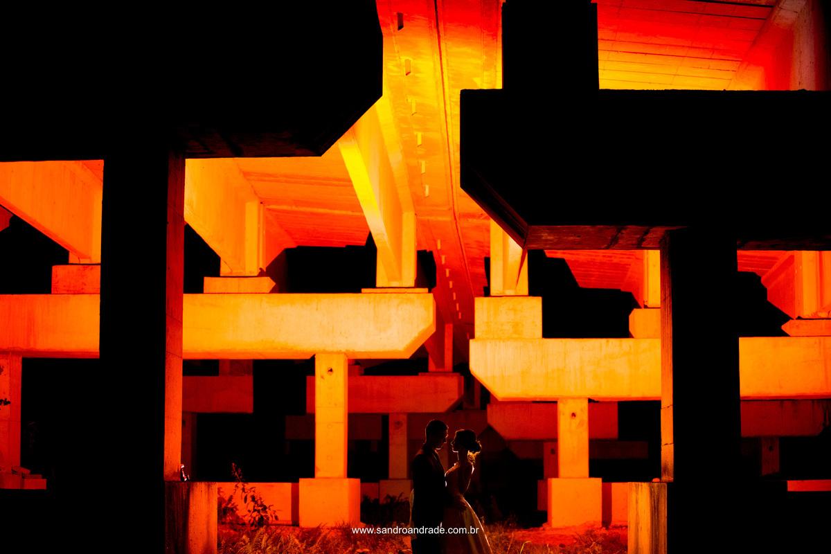 Fotografia entre as colunas em baixo de uma ponte, com efeitos de luz e uma belissima silhueta de um casal apaixonado.