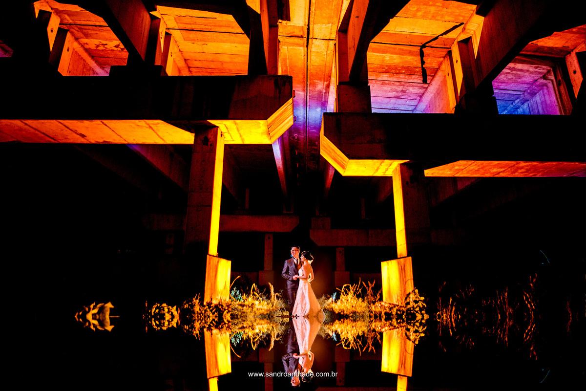 Reflexo, um casal enamorado e uma fotografia inusitada entre pilastras e luz amarela.
