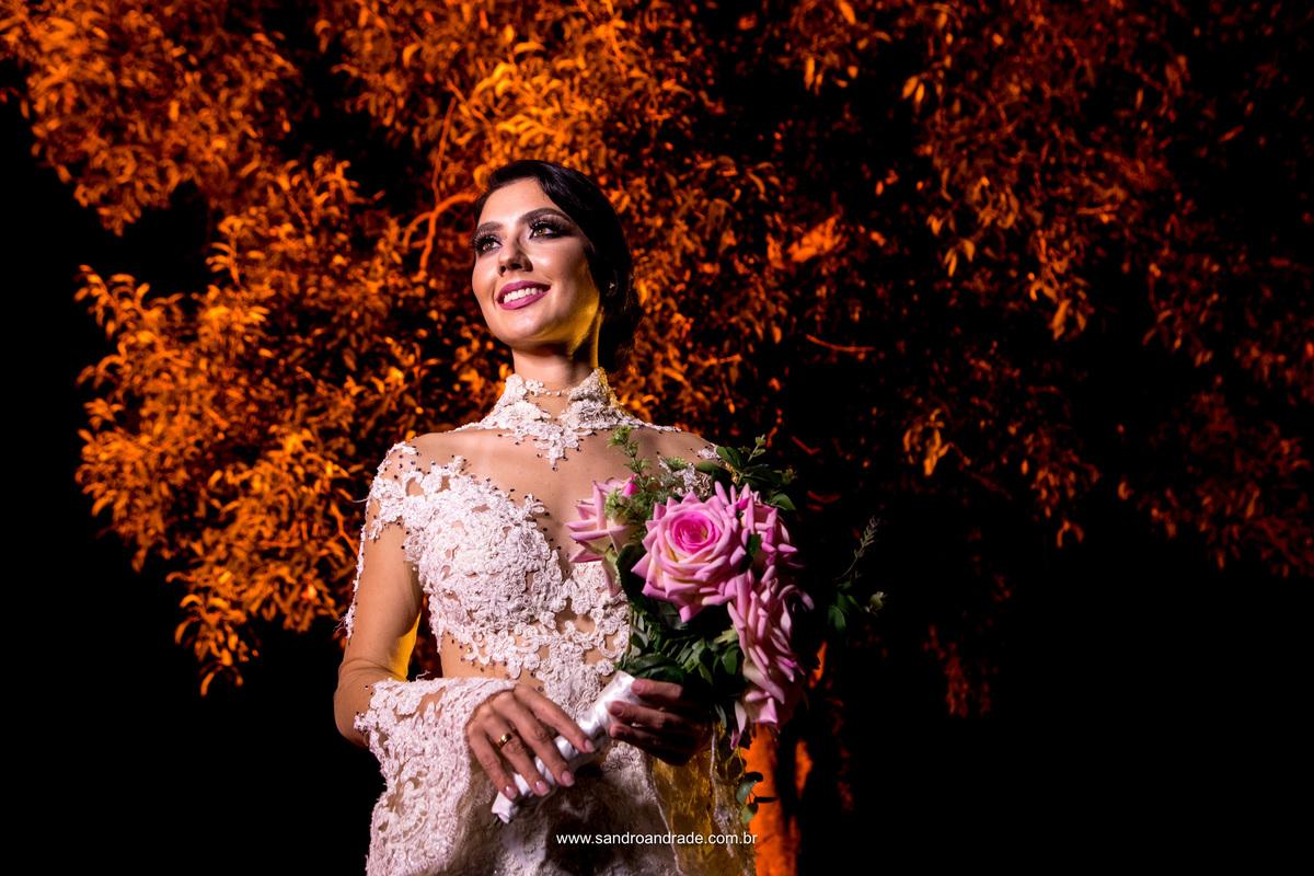 A noiva exuberante, linda, delicada em um belissimo vestido cheio de transparencias, com um lindo buque de rosas, um retrato belissimo de uma noiva belissima.