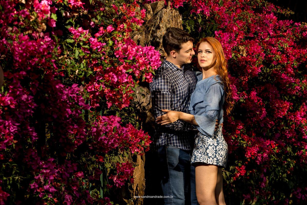 De tirar o fôlego esta belissima fotografi, o casal em tons de azul, ela com seus cabelos ruivos, em meio as bougainviles rosa choque.