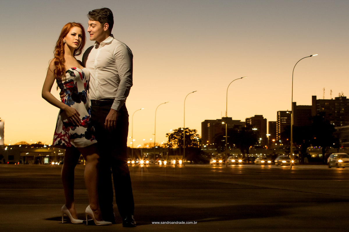 O casal posa para fotos no Plano Piloto de Brasilia, com um lindo céu de por do sol ao fundo.