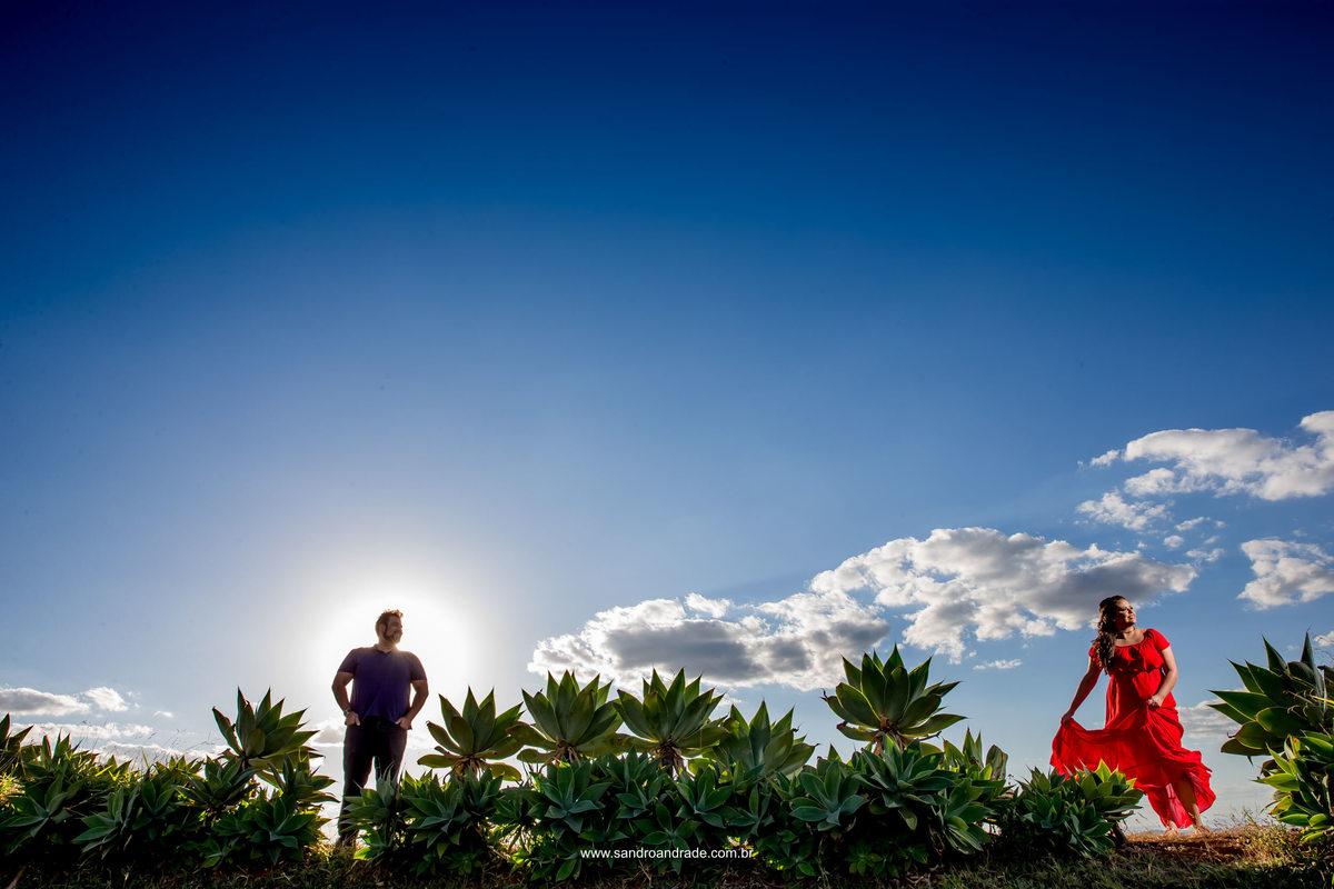 Foto top...o noivo em silhueta e a noiva em destaque com um lindo vestido vermelho em contraste com o azul do céu.