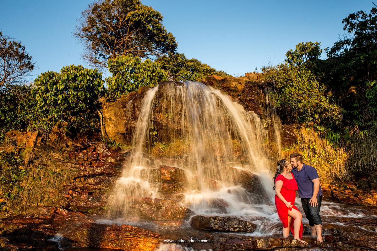 Uma cachoeira linda com uma fotografia em efeito de baixa velocidade e Helena e David no canto direito, lindos com os p'[es dentro d'agua.