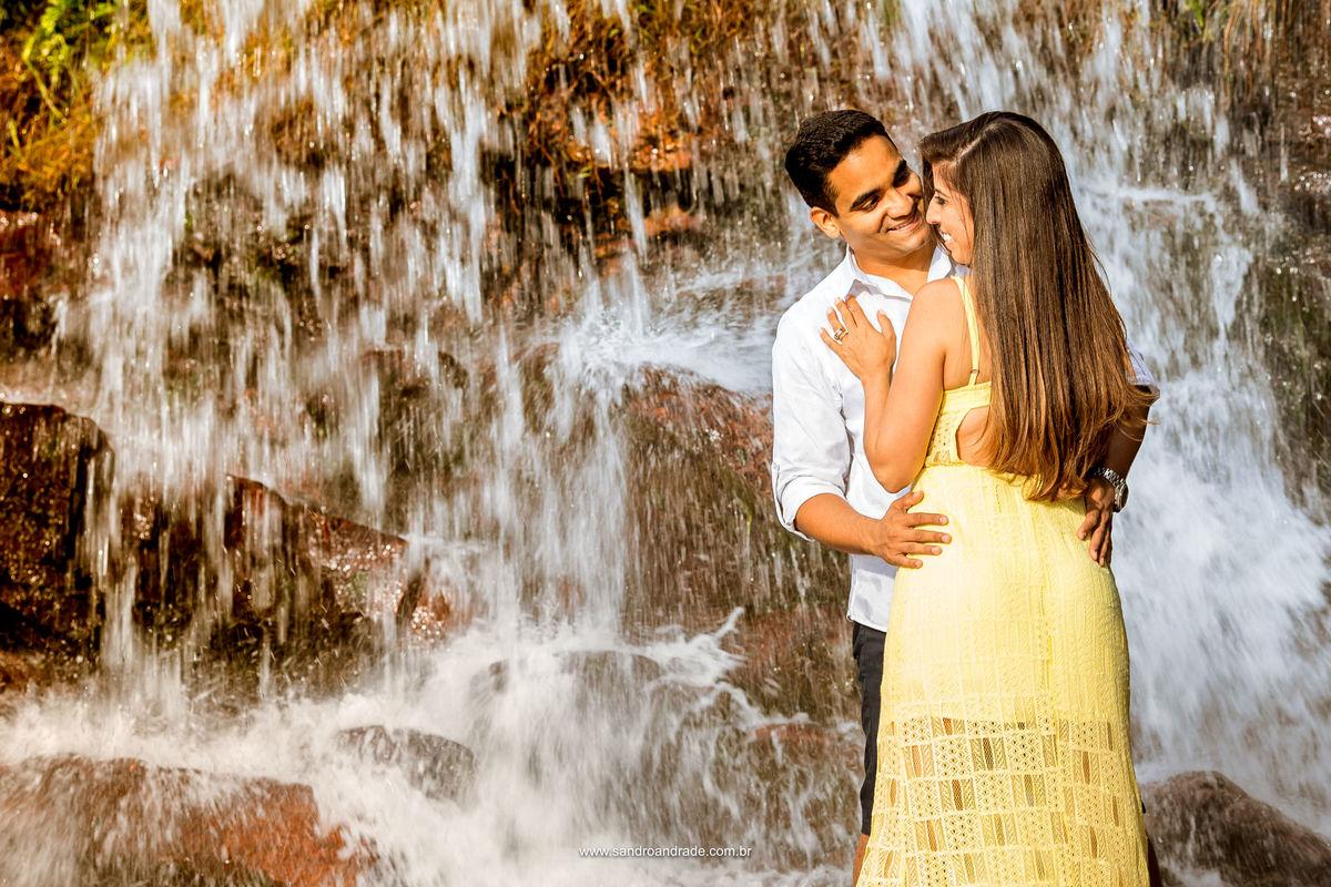 Fotografia colorida deste maravilho casal, ao fundo a cachoeira com efeito de baixa velocidade.