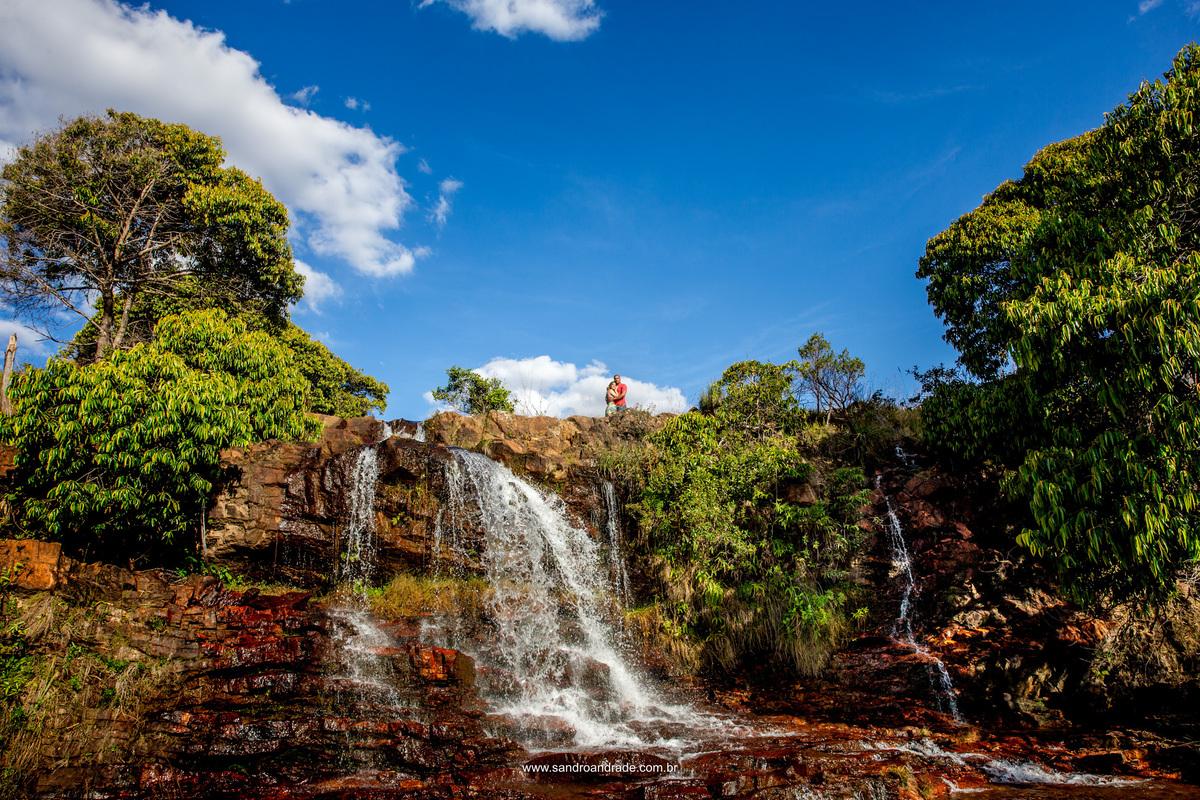 Linda fotografia colorida, deste lindo casal, com a cachoeira e minimalismo, natureza e amor.