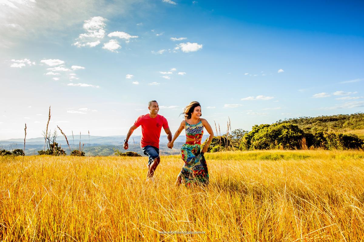 Na grama alta eles correm de mãos dadas, sorriso descontraído.