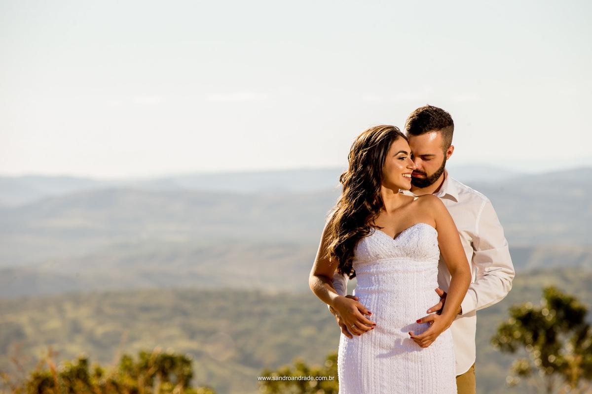 Fotografia colorida de um casal prestes a se casar, realizando o ensaio romantico com o fotografo de casamentos sandro andrade e lindas montanhas ao fundo em uma fotografia colorida.
