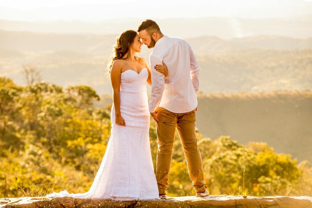 Em uma pose inusitada o noivo de costas em direção ao belo serrado e a noiva de frente para as lentes de Sandro Andrade, eles se viram em direção ao outro, muita ternura nesta foto colorida.