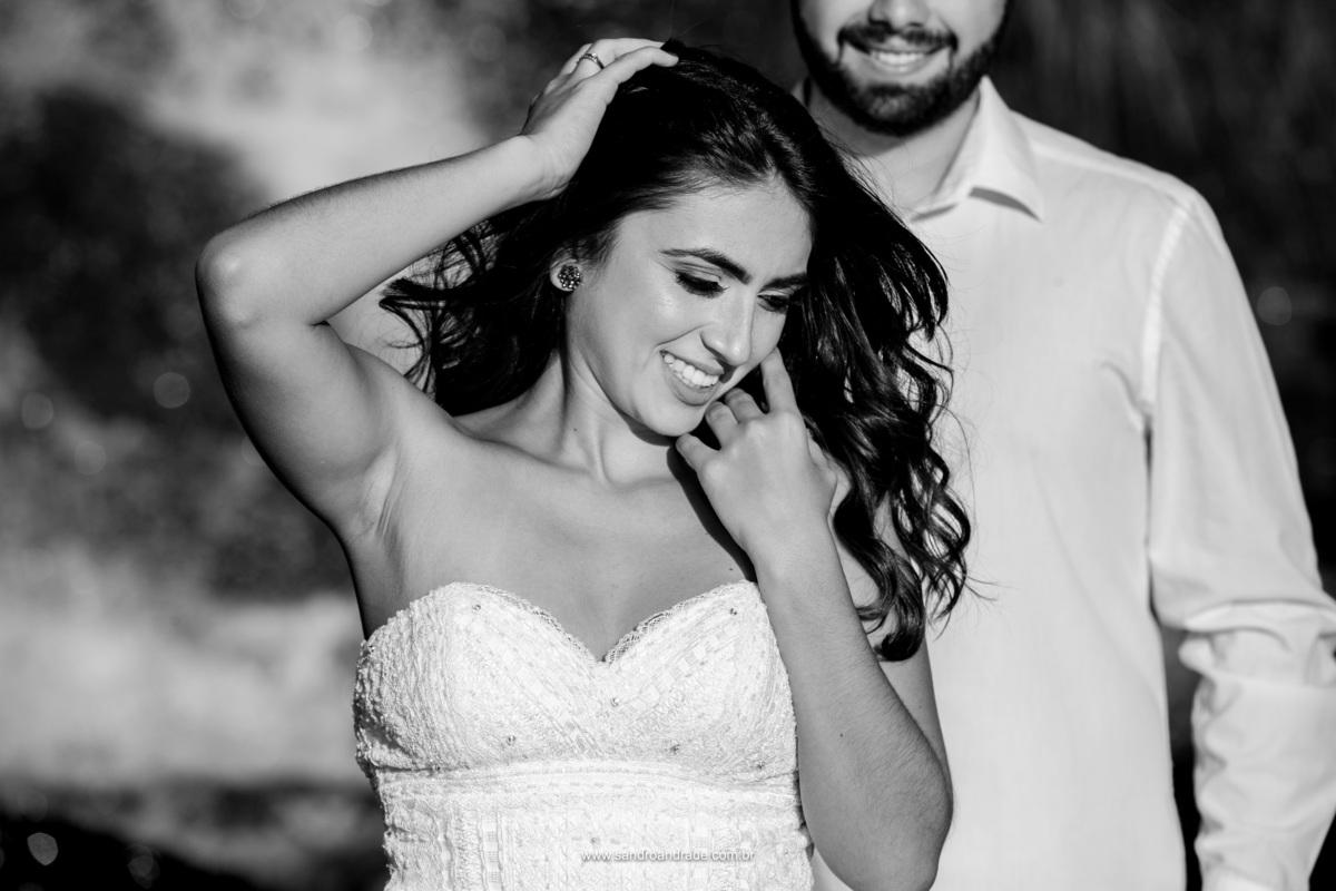 Retrato da noiva mexendo em seu cabelo e o sorriso do noivo ao fundo compondo esta fotografia preto e branco.