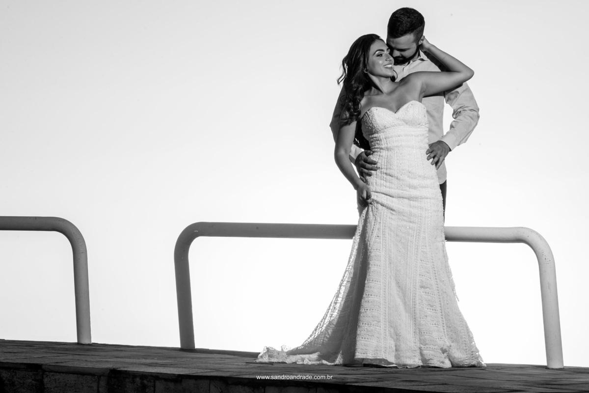 Apenas o casal bem juntinhos, sorrindo, tudo super exposto nesta fotografia preto e branco.