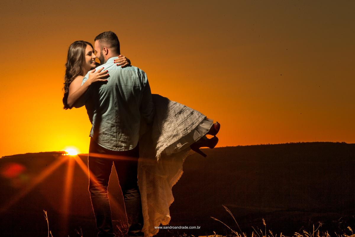 Sua amada em seus braços eles fazem juras de amor, sorrisos, um colo terno, olhar apaixonado e sorrisos bobos em composição com este belo por do sol e um lindo flair.