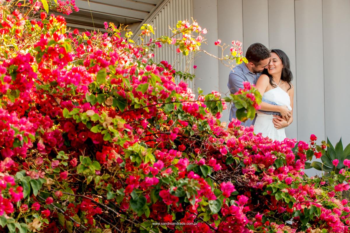 Retrato dos noivos no meio de lindas flores do pé de bougainville, com sorrisos descontraidos, sinceros e espontâneos.
