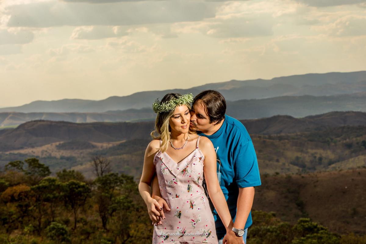 Retrato de Daianne e Eduardo, ele beija a sau amada no rosto e ao fundo a natureza exuberante do Paraíso na Terra, com montanhas e todo o cerrado.