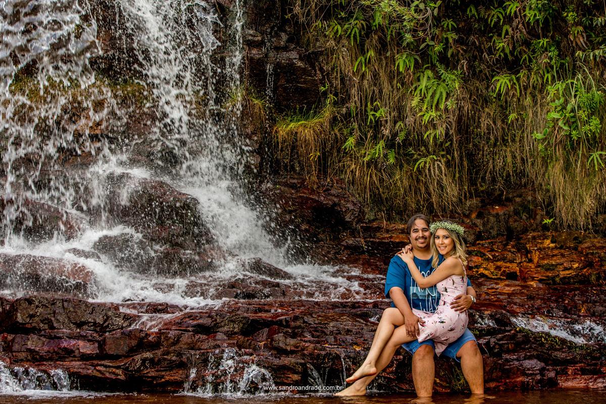 Na cachoeira os dois apaixonados olham para a foto de Sandro Andrade fotografo de casamentos em Bsb. Na cachoeira Eduardo coloca sua amada em seu colo.