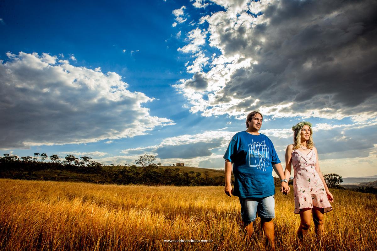 Os noivos caminham juntos entre o mato seco comum desta epoca do ano aqui no DF, com um lindo céu azul repleto de nuvens para compor esta belíssima fotografia.