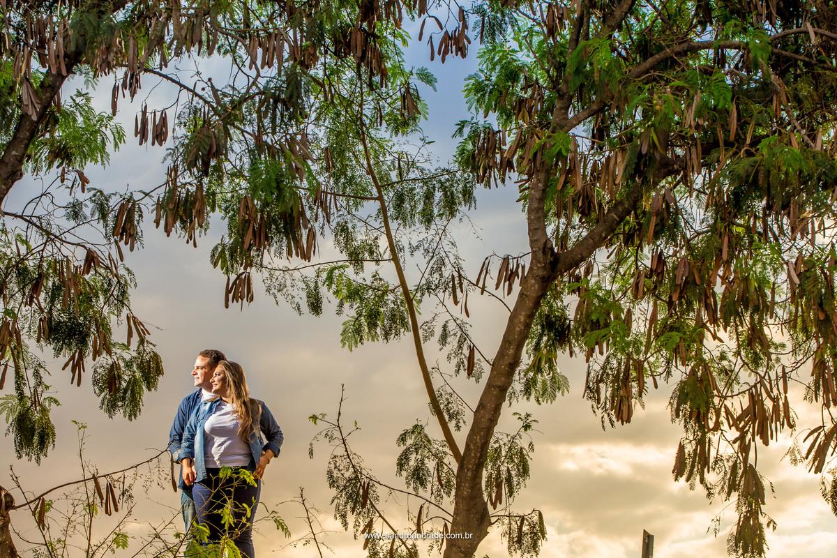 Entre as arvores Gabi e Marcos olham na mesma direção, ao fundo o azul e amarelo no céu e o verde da arvore.
