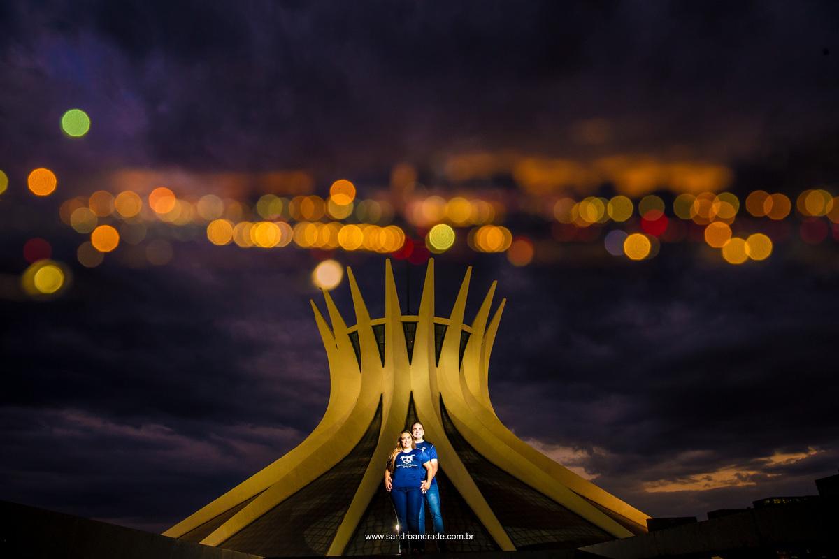 Esta fotografia foi um pedido de Gabi e Marcos, com a camisa da paróquia que fazem parte e lembrando que se conheceram la, eles posam para uma linda foto colorida na frente da catedral de Brasilia, linda em tom amarelo e um céu roxo ao fundo.