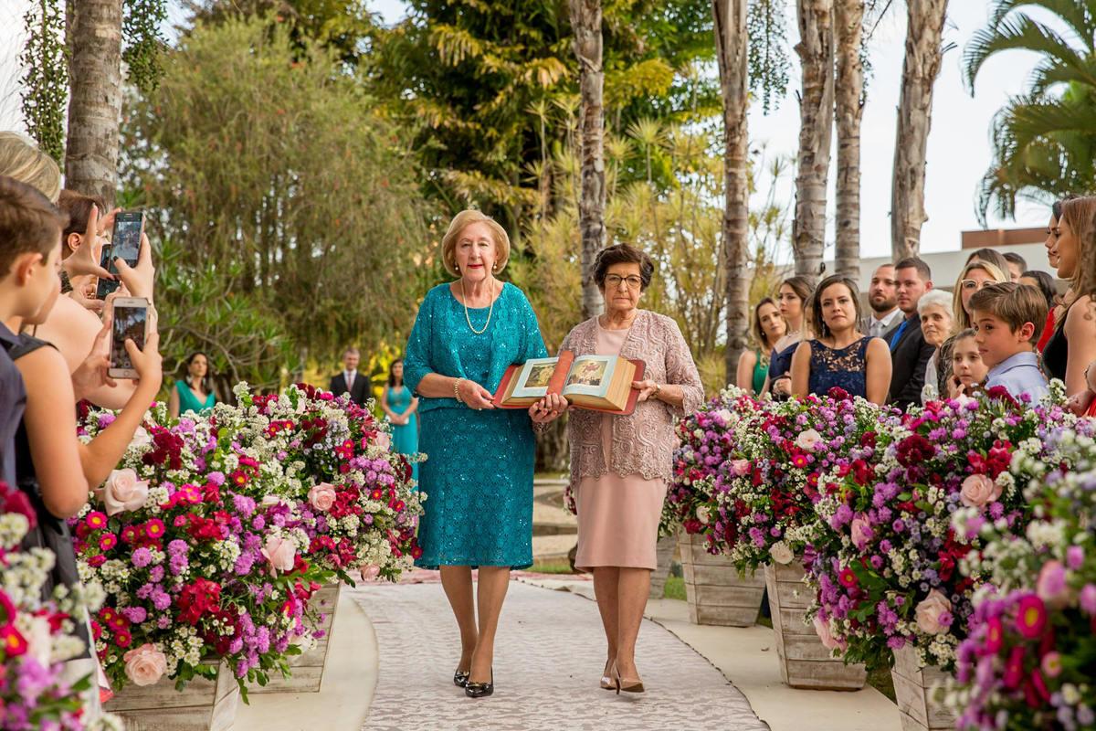 Para a benção matrimonial, as avós dos noivos conduzem a bíblia ao altar.