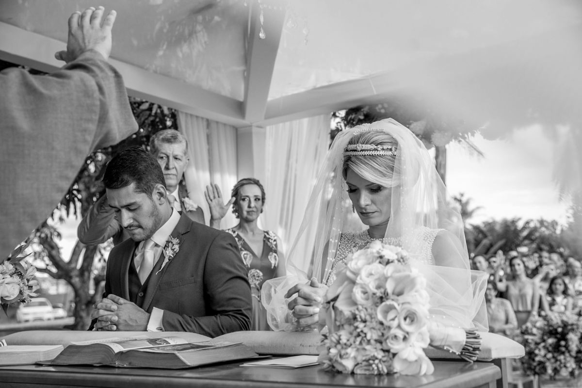 O momento da benção sobre a vida do casal é muito lindo e importante, os pais erguem as mãos sobre seus filhos, padrinhos e convidados ao fundo também abençoa o casal, tudo composto em uma linda fotografia preto e branco.
