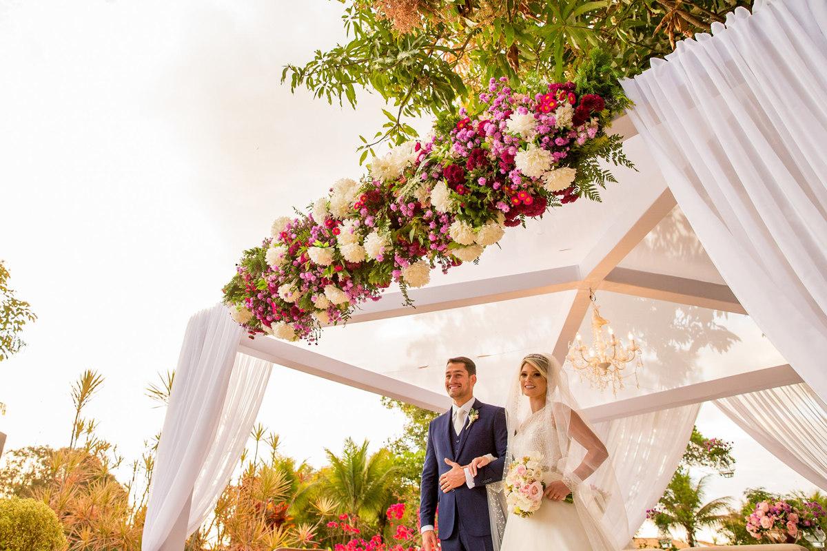 Se preparando para a saída e de braços dados, os noivos olham felizes para os seus convidados.