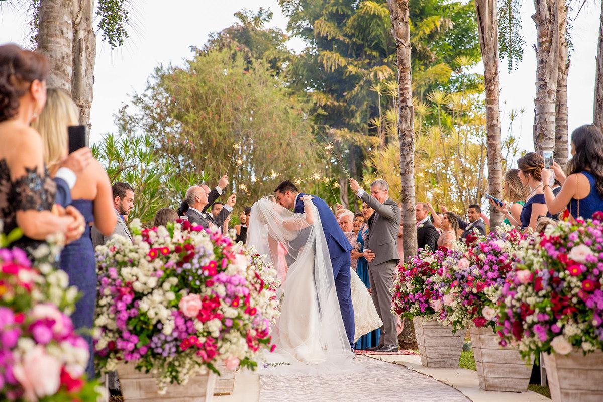 Em meio ao cortejo do casamento na saída os noivos se beijam, um lindo beijo de novela.