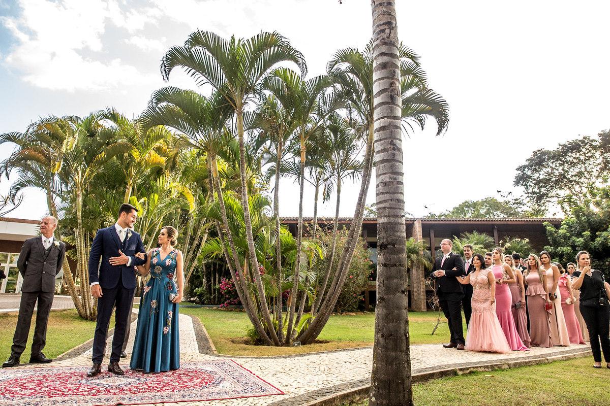 Posicionados para o cortejo, o noivo de braço dado com sua mãe, o pai da noiva já aguardando a chegada de sua filha e os padrinhos já em fila.