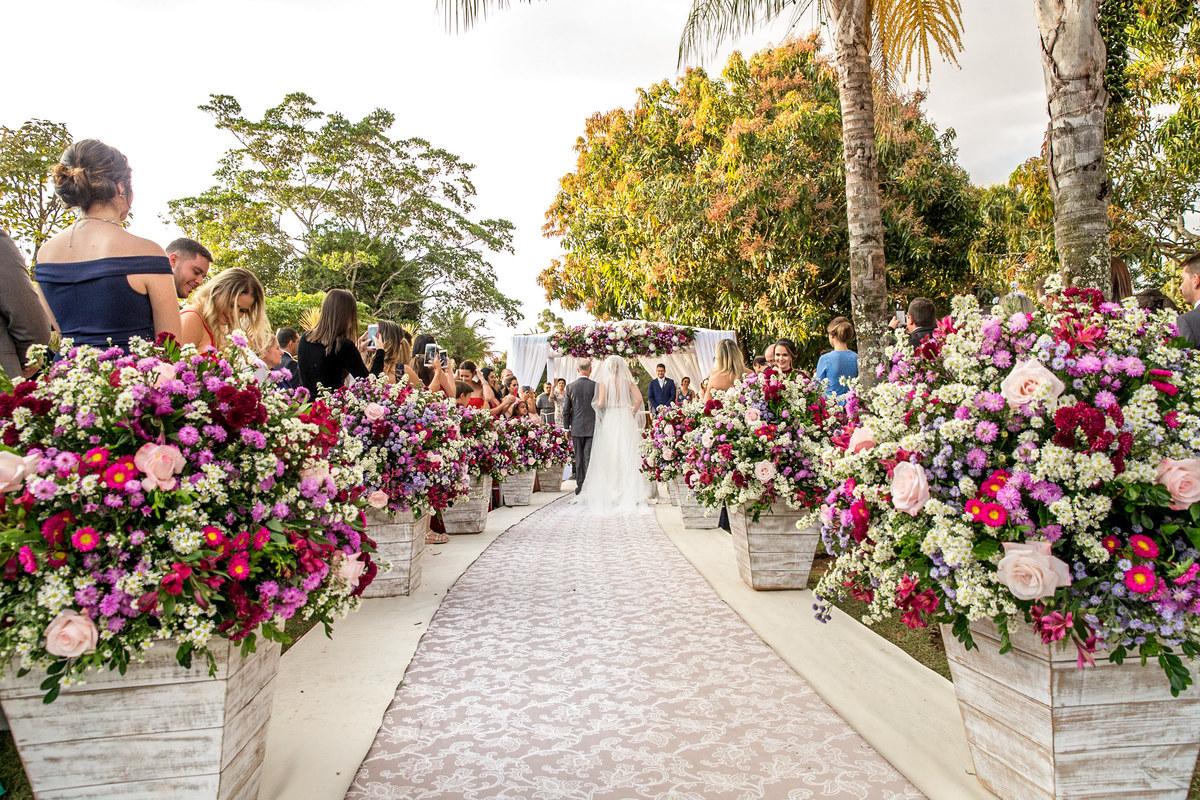 Um registro da entrada da noiva de costas, pegando toda a decoração da cerimonia, os pais e o noivo no altar.