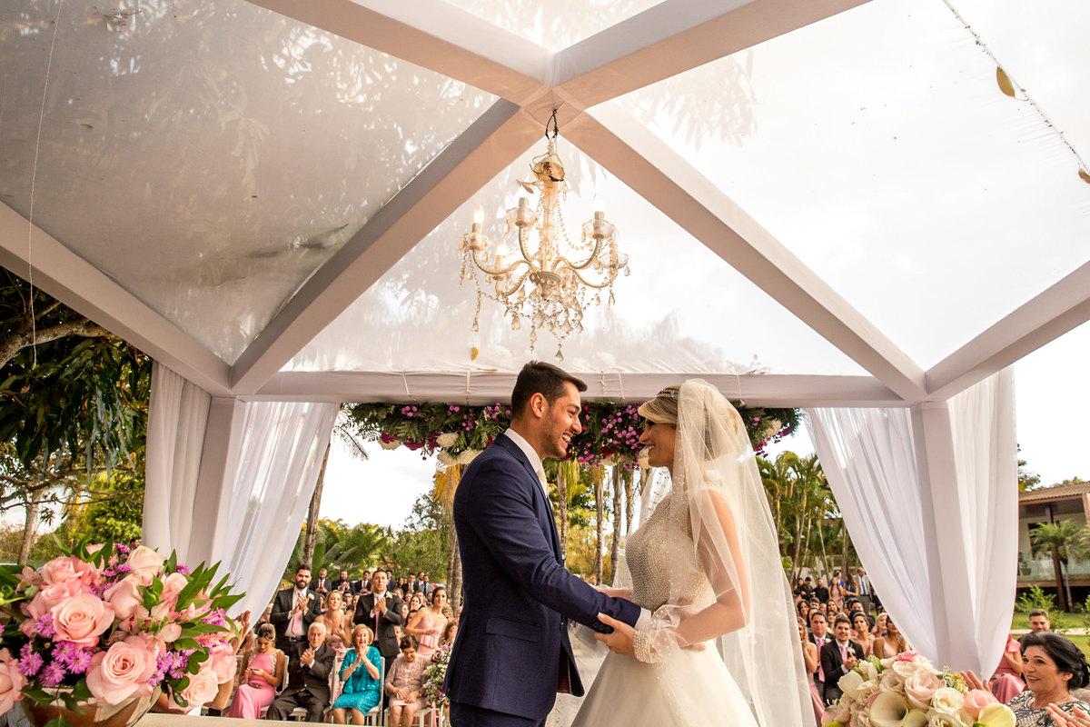 Apaixonados, eles se olham antes do tão esperado beijo no altar, com os amigos e familiares batendo palmas no fundo.