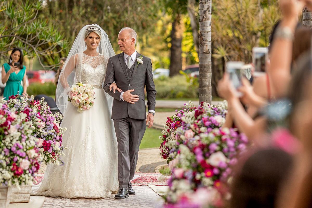 O pai entrando com sua filha, a admira, encantado com a sua bela filha e o belo vestido de noiva do atelier da estilista Neimar Sinício.