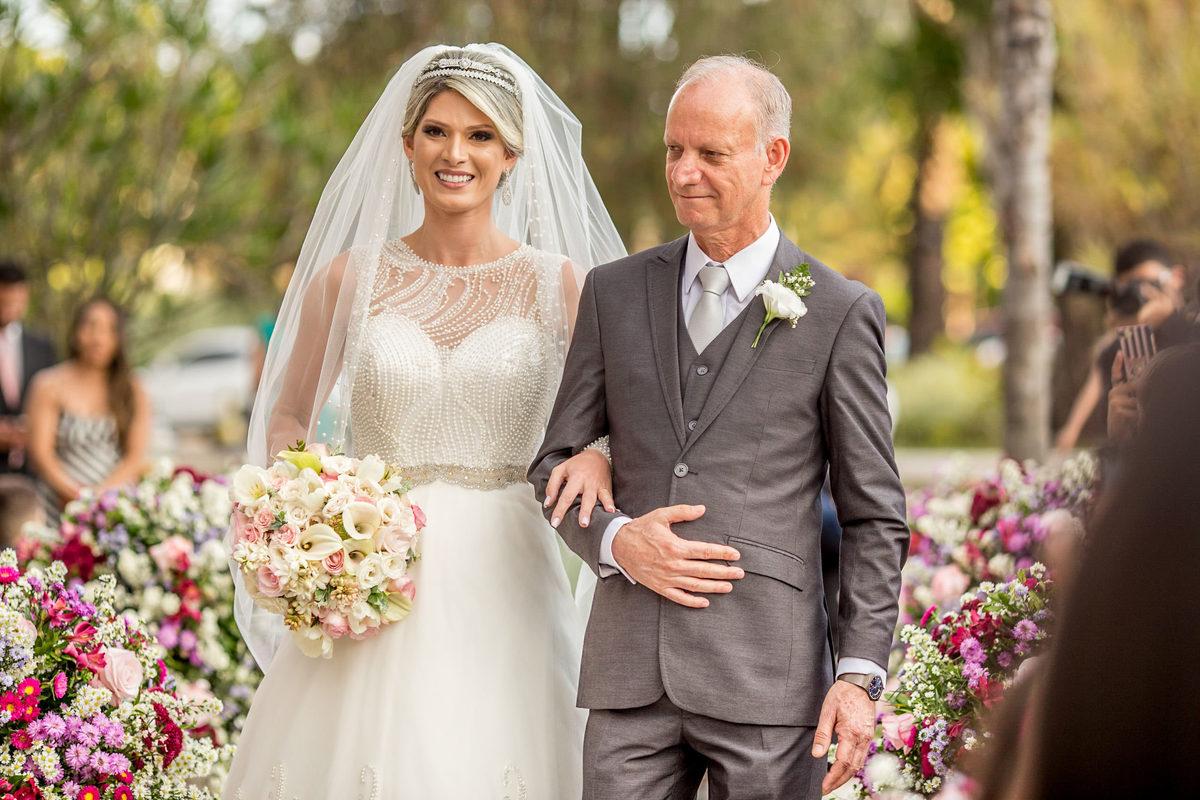 A entrada da noiva com seu pai, felizes eles sorriem.