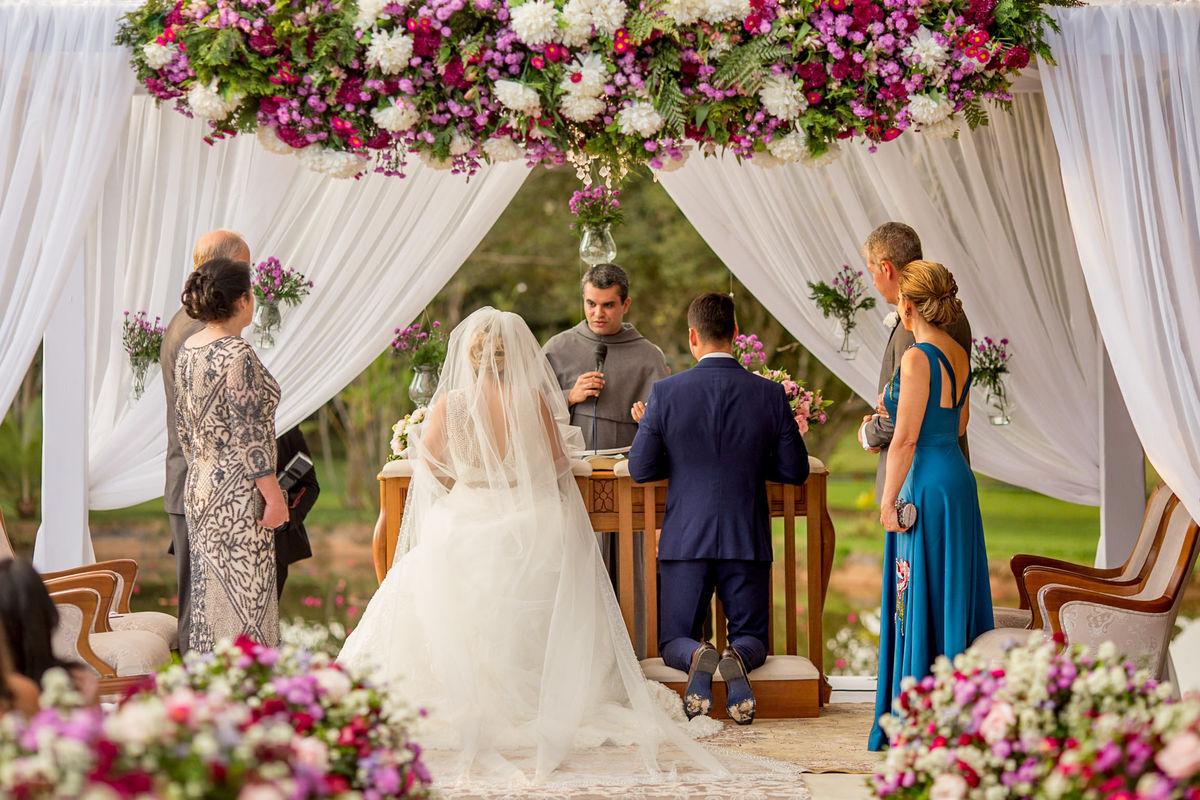 Os pais e os noivos no altar já ajoelhados, eles recebem as palavras finais do padre.
