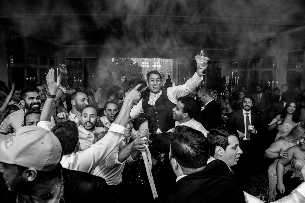 O noivo sendo carregado por seus amigos, uma fotografia muito massa de momento, em preto e branco.