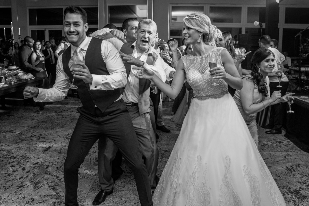 O casal dançando junto com alguns convidados e o pai do noivo fazendo coreografia com ele.