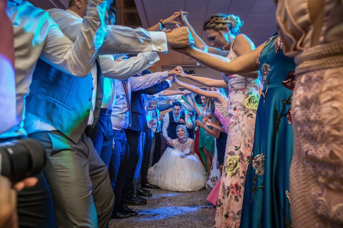 Amigos e parentes fazem um corredor no meio da festa para o casal passar.