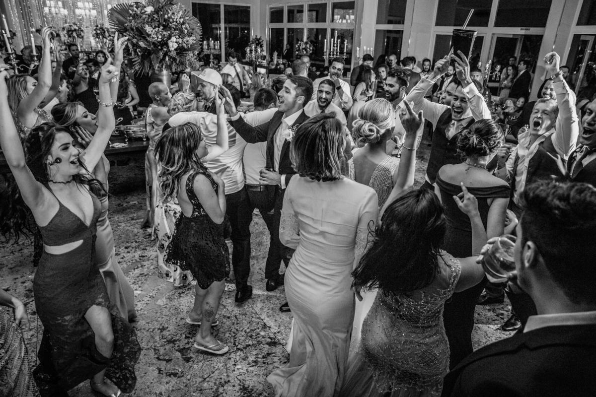 Se jogando na boate do casamento, o noivo toca um instrumento e todos dançam ao redor dele e da noiva.
