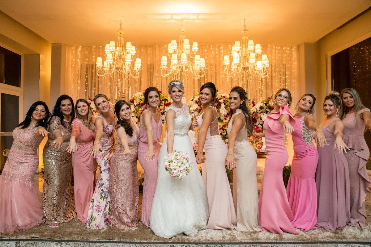 A noiva com todas as suas madrinhas na mesa do bolo, fotografando com o buquê.