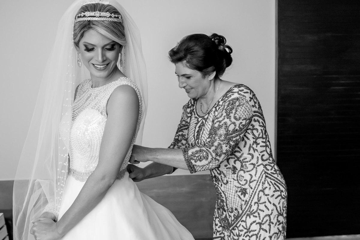 Cecília e sua mãe, em uma linda fotografia preto e branco, a mãe da noiva está fechando o vestido de sua linda filha.