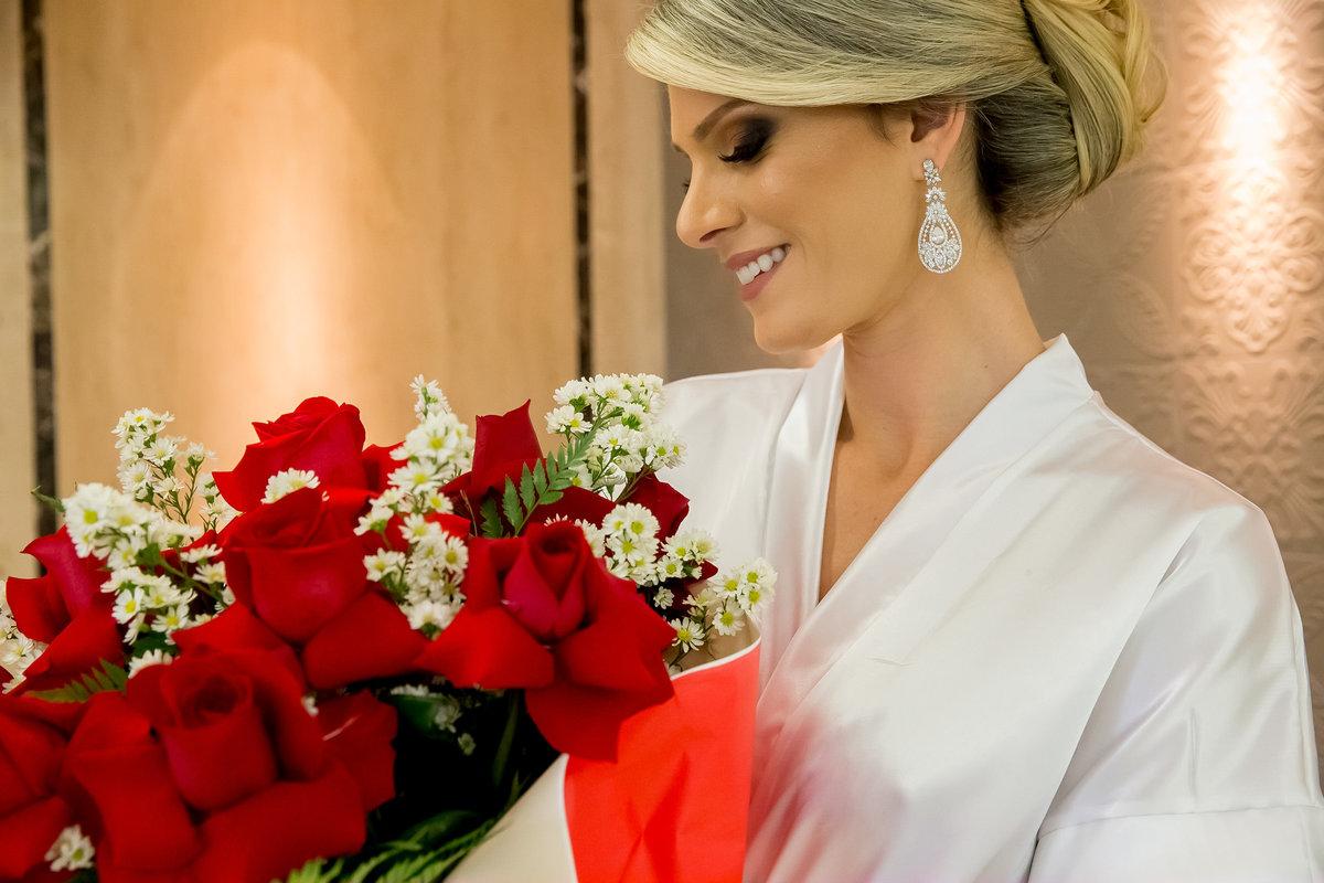 Já pronta a noiva Cecília, admira o buquê que o seu noivo a presenteou.