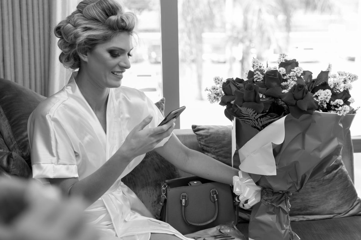 Feliz com seu buquê de rosas, imediatamente ela pega o celular para fazer uma foto.