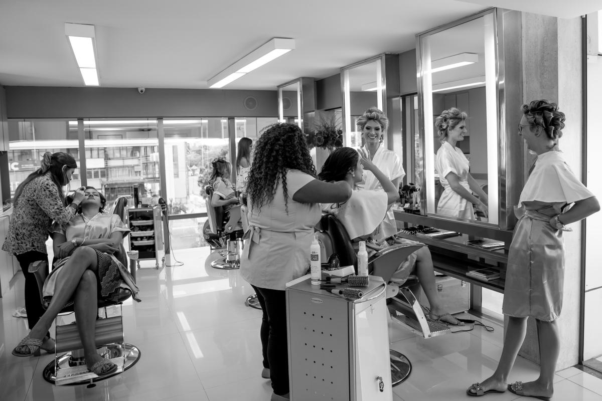 Já no salão para o making of da noiva...todas as madrinhas estão arrumando o cabelo e fazendo a maquiagem, enquanto a noiva aguarda sua vez, ela observa tudo atentamente e sorridente.
