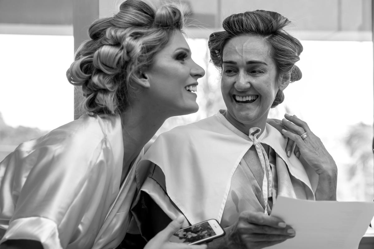 Emocionadas noiva e sogra, sorriem após ler a mensagem do homem de suas vidas, uma a noiva e outra a mãe.