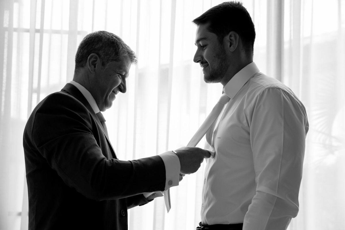 Uma fotografia preto e branca, com um lindo contra-luz a frente da janela o pai de Marcos arruma a gravata dele.