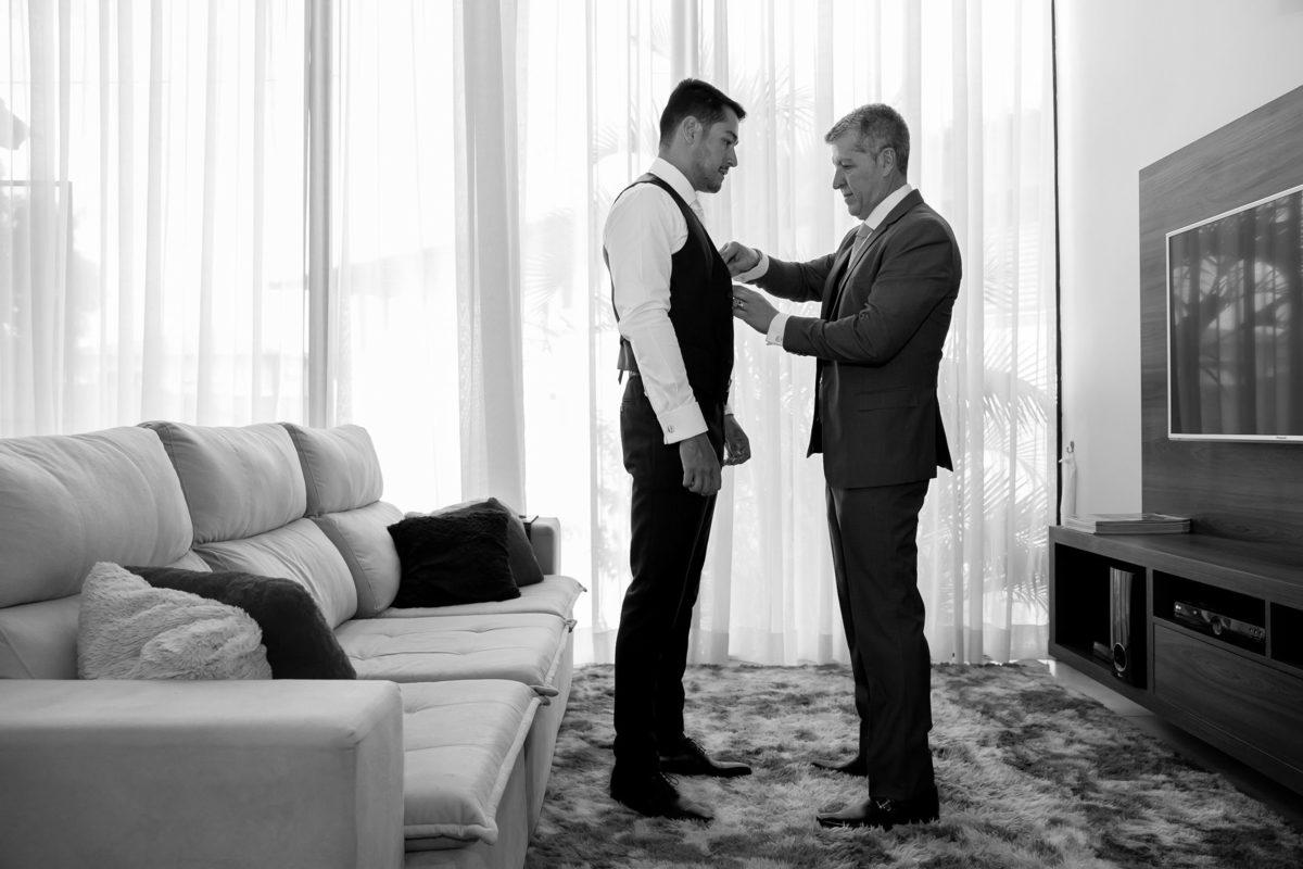 Ajeitando os detalhes no traje do noivo, o pai carinhosamente arruma seu filho.